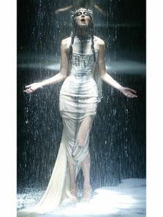 """McQueen let it rain on the runway during his Fall 2004 American Express """"Black"""" show — which also included an auction of celebrity memorabilia to aid people living with AIDS. While most designers wouldn't want their creations soaked, the designer allowed the rain to highlight his white, diaphanous ensembles."""
