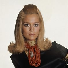 Lauren Hutton is wearing black satin cossack's blouse, coral necklaces and owl pin from Tiffany, photo by Bert Stern. Love her hair here.