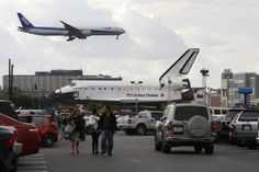 A jet lands at Los Angeles International Airport (LAX) behind the space shuttle Endeavour during a break in its movement as it is transported from LAX to the California Science Center in Exposition Park where it will be on permanent public display on October 12, 2012 in Los Angeles, California. Endeavour was flown cross-country atop NASA's Shuttle Carrier Aircraft from Kennedy Space Center in Florida to LAX on its last flight ever on September 21. Completed in 1991, Endeavour was built to…