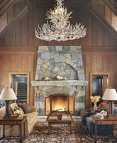 Wood paneled living room with vaulted ceilings, an enormous antler chandelier and striking stone fireplace and mantel create a space that is the ultimate in rustic decor chic.