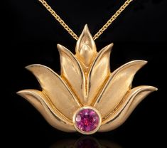 "This lotus flower pendant necklace is 14k yellow gold with a pink tourmaline stone. It has a hidden bail which allows for it to fall simply and beautifully on the neck. It measures approximately 1"" x 1"" and comes with an adjustable 16- 22"" coordinating cable chain. This piece also comes in a 1/2"" size. Please check other listings for details"