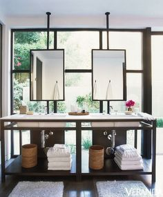 Sleek bathroom design with ceiling mounted hanging mirrors over contemporary double vanity placed in front of floor to ceiling steel windows. Master bathroom features metal double vanity with his and her sinks and shelving filled with towels and his and her bath mats.