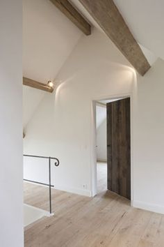contemporary country architecture - pale wooden floor and beams, white walls and simple iron banister detailing - Corvelyn - Realisaties - Landelijke woning
