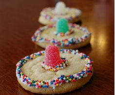 Fiesta Party ideas Sombrero Cookies - Make a quick and easy sombrero cookie by piping white frosting around the edges of a sugar cookie and in the center to hold the gumdrop.  Place a large gumdrop in the center of the cookie and then add colorful sprinkles to the frosting.
