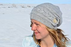 Song of Winter Slouch Hat is a cable knit hat pattern. The cable knit band on the knit hat is knitted first and then stitches are picked up from there. Click through to see this hat on Ravelry from KnotEnufKnitting.