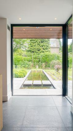 Doorkijk vanuit de woonkeuken door een glazen pui richting tuin met lange smalle vijver.