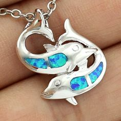 This dolphin swim team features striking blue or white fire opals crafted in blue fire opal and set in sterling silver. PENDANT DETAILS - Pendant length: 7/8 in. - Chain length: 18 in, 20 in, 22 in or