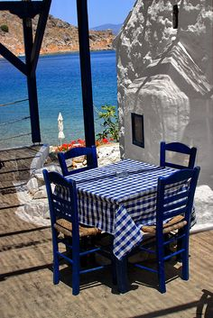 Waterfront taverna and church  Taverna's table and church overlooking the sea. Mandraki, Hydra island, Saronic, Greece