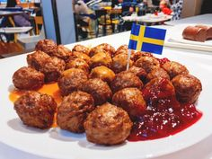 Fresh tasty meatballs with cranberry sauce on white plate with S