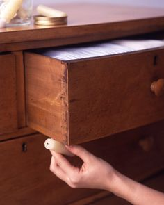 Rubbing a candle on old wooden drawers for easy sliding
