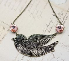 """Retro Pink/Peach Bird Necklace 16""""      An elegantly crafted large 2 1/4"""" x 1 1/2"""" antique brass bird is the heart of this beautiful necklace. 10mm peach/pink jewels add a pop of color and add to the vintage inspired beauty of this unique piece.  16"""" antiqur brass chain."""