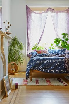 Oh, this is so pretty. The blues, plant greens, and wispy lilac curtains. So breezy, clean, warm...And the wood floors, too.