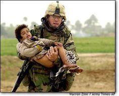 Iraq War - American Soldier carrying Iraqi child