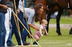 Great escape: Prince George wriggles in the Duchess of Cambridge's arms as he attempts to go for a crawl on the polo field - despite the presence of polo ponies