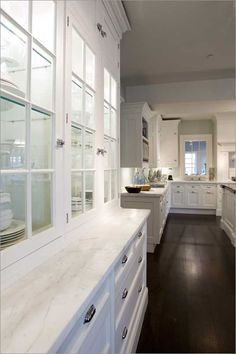 glass-front cabinets, lit inside + white marble countertops + cabinet & drawer hardware