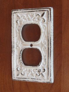 White Decorative Electrical Outlet Plate /Plug-in Cover/ Fleur de lis/ Bright Cast Iron/ Shabby Chic/Nursery Decor. $8.99, via Etsy.