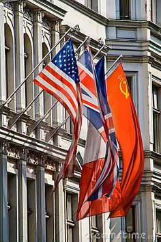 Historical flags of USSR, France, England, USA in front of Checkpoint Charlie Museum, Berlin, Germany