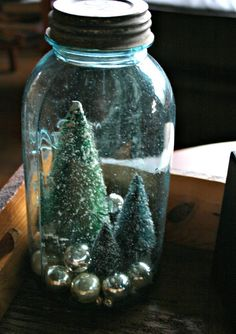 trees in ball jar   ... from among vintage silver ornaments in a large blue Mason jar