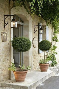 French Country Home | Topiaries, stonework and black scrolled iron on the light fixtures create a breathtaking entry that is still a little bit understated.