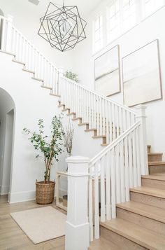 Cottage foyer designed with staggered art on a staircase wall above wood stairs and white spindles. Staircase Wall Decor, Stair Art, Foyer Staircase, White Staircase, Staircase Remodel, Staircase Makeover, Entrance Foyer, Staircase Design, Stairway Walls