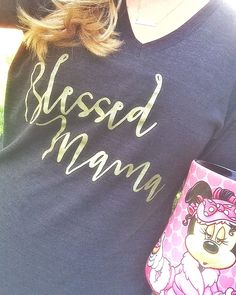 Blessed Mama printed in gold on a charcoal grey tri-blend vneck tshirt. Shirt is very soft and comfortable. Shirt is a unisex shirt and is very loose and long. I would not suggest sizing up but if you want a tighter look I suggest sizing down. Tri-Blend (50% Polyester / 25% Cotton / 25% Rayon) c...