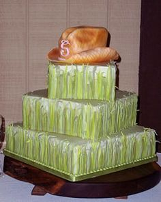 hree tier western style, square green wedding cake with a handmade orange fondant cowboy hat made of cake. The cake is decorated with grass made of fondand around each tier. From www.tiffanysbakingco.com