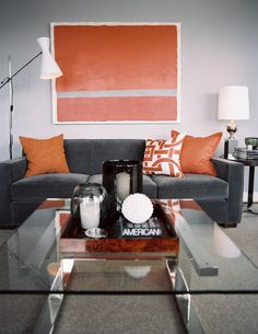 A glass-topped coffee table paired with a gray couch and orange pillows