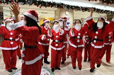 Dancers clad in Santa Claus outfits performs as part of a flash mob event to enjoy Christmas shoppers at Tobu Department Store in Tokyo on December 19, 2014. Some 30 dancers took part in the Christams event.