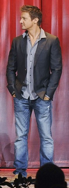 Jeremy Looking to the Right and Wearing a Gray Open-Necked Button-Up Shirt, Dark Gray Jacket and Blue Jeans
