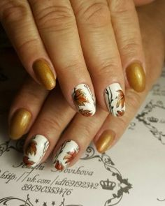 Beautiful winter nail art design in gold and white. The nails showcase falling leaves on its design, you can also see gold dust on the other nails that softly contrast the white base beneath the fall leaves.