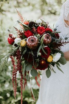 a red protea wedding bouquet with berries, thistles and cascading blooms Protea Wedding, White Wedding Flowers, Purple Wedding, Boho Wedding, Floral Wedding, Fall Wedding, Bouquet Wedding, Wedding Ideas, October Wedding