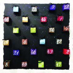 Un calendrier de l'avent.  Réalisé avec des feuilles de scrapbooking spéciales noël et pailletées (boîtes), des stylos pen touch argent et blanc (écriture des chiffres), une paire de ciseaux et de la colle pour monter les boîtes, du ruban en velours noir pour fermer les boîtes, des œillets argent et blanc pour faire passer le ruban, des pochoirs pour les chiffres, un châssis, de la peinture noir, de la paillette noir et de la peinture structure pour un contour effet neige.