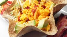 A crispy flour tortilla bowl is topped with egg, cheese, avocado, and salsa in this quick and easy breakfast bowl, done in 20 minutes!
