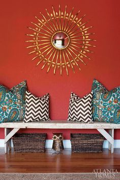 red walls ~ gold sunburst mirror ~ teal paisley and black and white chevron throw pillows ~ simple bench ~ rustic baskets ~ owl ~ awesome, colorful design