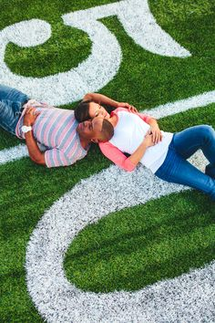 50 yard line engagement photo for a football coach and his fiancée. Photography by thegoodness.com