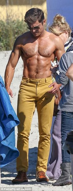 Not a bad tan either: Zacs tight yellow jeans and no shirt look was easily the most sane outfit he has worn on this film yet