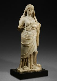 ROMAN MARBLE STATUE OF A WOMAN, POSSIBLY FAUSTINA II AS A GODDESS.    Standing in a relaxed pose, her weight on her right foot. She wears the stola and palla worn capite velato over a diadem.         2nd half of the 2nd Century AD.