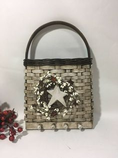 This key wall basket would look great hanging on the wall by your entry door. It has 4 wooden pegs on the bottom of the basket where you could hang your keys. The inside of the basket could hold your mail or some pretty dried flowers. It is painted white and then distressed. It is then