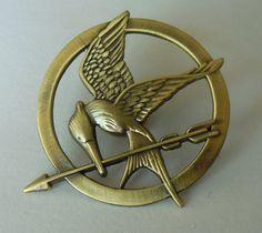 Als cadeau van haar enige vriendin krijgt Katniss een speld. Deze speld draagt Katniss in de arena. Later gaat de speld, in het laatste boek, het symbool zijn van de revolutie.