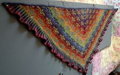 A colourful triangular shawl knitted from the centre back neck in a very special yarn with long colour changes