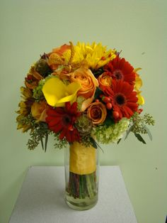 fall colors of yellow callas, orange gerbers, green hydrangea, mokara orchids and sunflowers