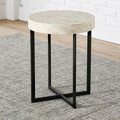 "Material mix. Simple and sculptural, the Bone Side Table is a go-anywhere accent piece that combines an industrial-looking iron crossed base with the softer vibe of a natural bone-tiled top.  • 17""diam. x 22""h. • Iron base with powder-coated steel legs."