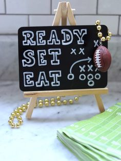 DIY food station sign using a small chalkboard on an easel with simple football-themed wording. Click or visit FabEverday.com for details on this and more of my football-themed décor ideas and resources. Pin this to your sports themed party planning boards! #diy #diyparty #partysign #diypartysign #chalkboard #easel #foodsign #footballdecor #footballparty #tailgateparty #gamedayparty #footballtheme #sportsparty #sportstheme #themedparty #themedparties #partyplanning #partyideas #fabparties