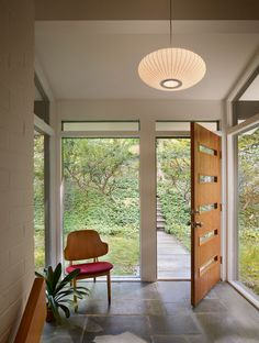 entry in a mid century house, white brick walls, George Nelson light, mid century chair, stone floor, vaulted ceiling, large windows, wood door with horizontal glass inserts