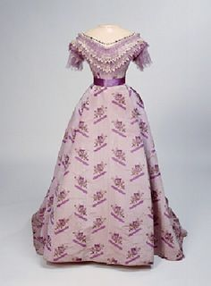 """1868-1870 Ballgown: Comprising a very complicated design which would have been difficult to manufacture, the silk from which this dress is made would have been exceptionally expensive. Almost certainly woven in France, it is printed with roses and """"trompe l'oeil"""" ribbons on a watered or moire ground.  So that she could use this outfit for both informal daytime events, the owner commissioned her dressmaker to provide two alternate bodices."""