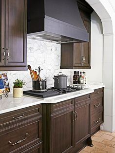 Classy!! / Smooth Elegance - Marble tiles cut in hexagonal and rectangular shapes make this smooth, elegant backsplash. Dark swirls in the marble match the matte black finish on the range hood and the dark wood finish on the nearby cabinets. Rather than serving as a focal point, this backsplash simply contributes to the sleek, elegant look of the room.