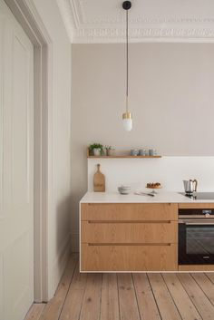 Modern Kitchen Kitchen of the Week: A Minimalist Galley Kitchen in a Georgian London Townhouse - Remodelista - Jack Trench Kitchens designed minimalist, cantilevered oak and Corian cabinets for a Georgian London townhouse with period details. Minimal Kitchen, Modern Kitchen Design, Kitchen Designs, Kitchen Island With Stove, Kitchen Small, Kitchen Ideas, Kitchen Oven, Kitchen Islands, Cooktops