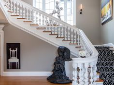 Edgy Design: Exaggerated banister spooling, a graphic black-and-white stair runner and edgy artwork bring a contemporary sensibility to the entryway. The neutral backdrop allows the artwork to take center stage.