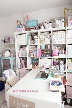 A giant ikea Kallax Unit and desk in a creative craft room. Full of vintage cabinets, mini storage boxes, wicker baskets and vanity cases being used as craft storage. Working from home is great when this is your home office!