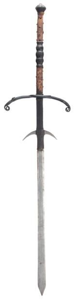German two-hand Processional sword, early 17th c. Long near-flat blade widening slightly towards a short spear point, an orb mark inlaid in latten on one side, long ricasso formed with a pair of slender forward-curved lugs and retaining its original leather covering over wooden fillets, blackened iron hilt of bars of diamond section, formed with a pair of long quillons with drooping ends terminating in slender tightly spiralling scrolls.